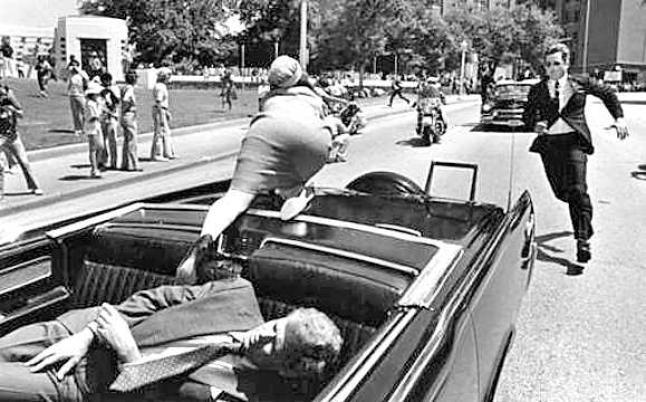Dallas, 23 de noviembre de 1963. El presidente John Kennedy yace muerto en el auto presidencial, mientras su esposa corre a la parte de atrás en busca de ayuda.