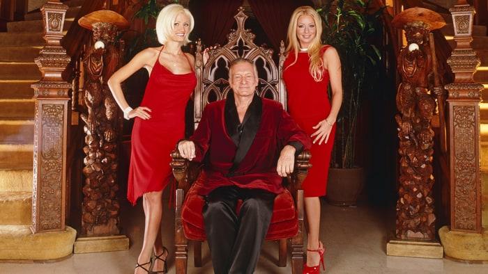 """Hugh Hefner posando junto a dos de sus """"conejitas"""" en uno de los salones de la mansión Playboy."""