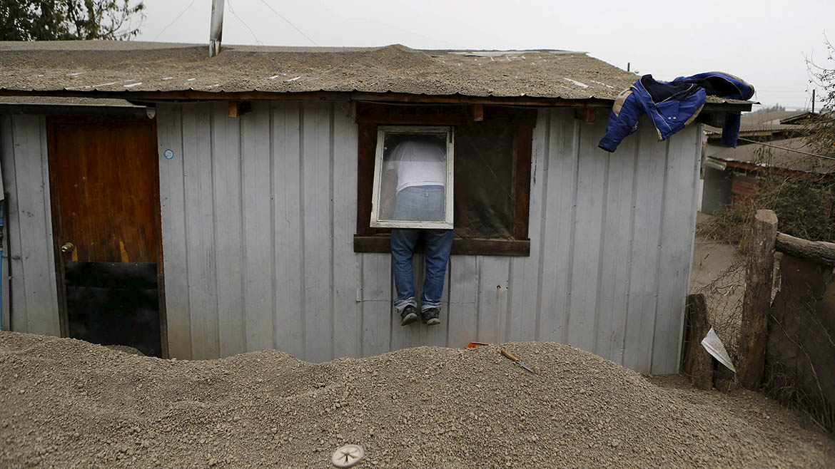A man uses a window to enter his house at Ensenada town which is covered with ashes from Calbuco volcano near Puerto Varas city