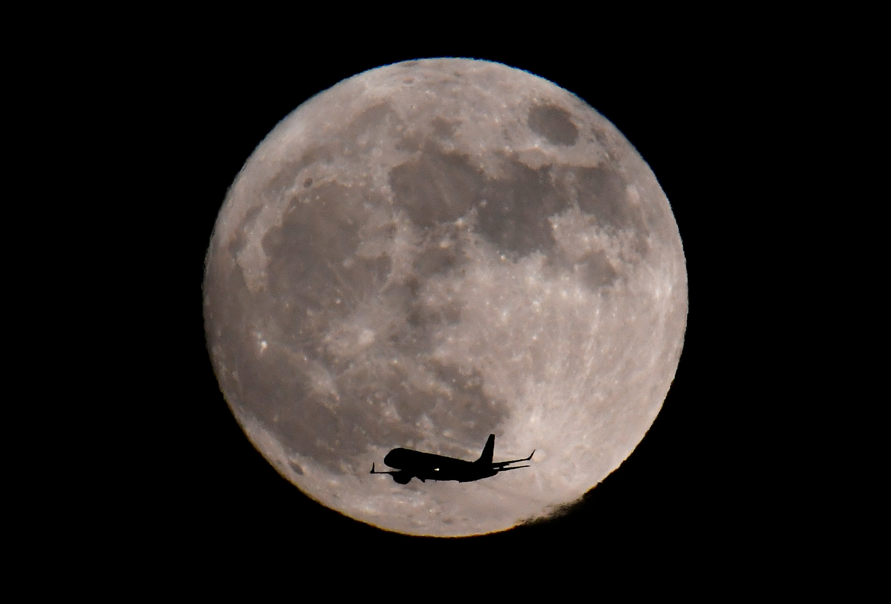 A passenger plane, with a 'supermoon' full moon seen behind, makes its final landing approach towards Heathrow Airport in London