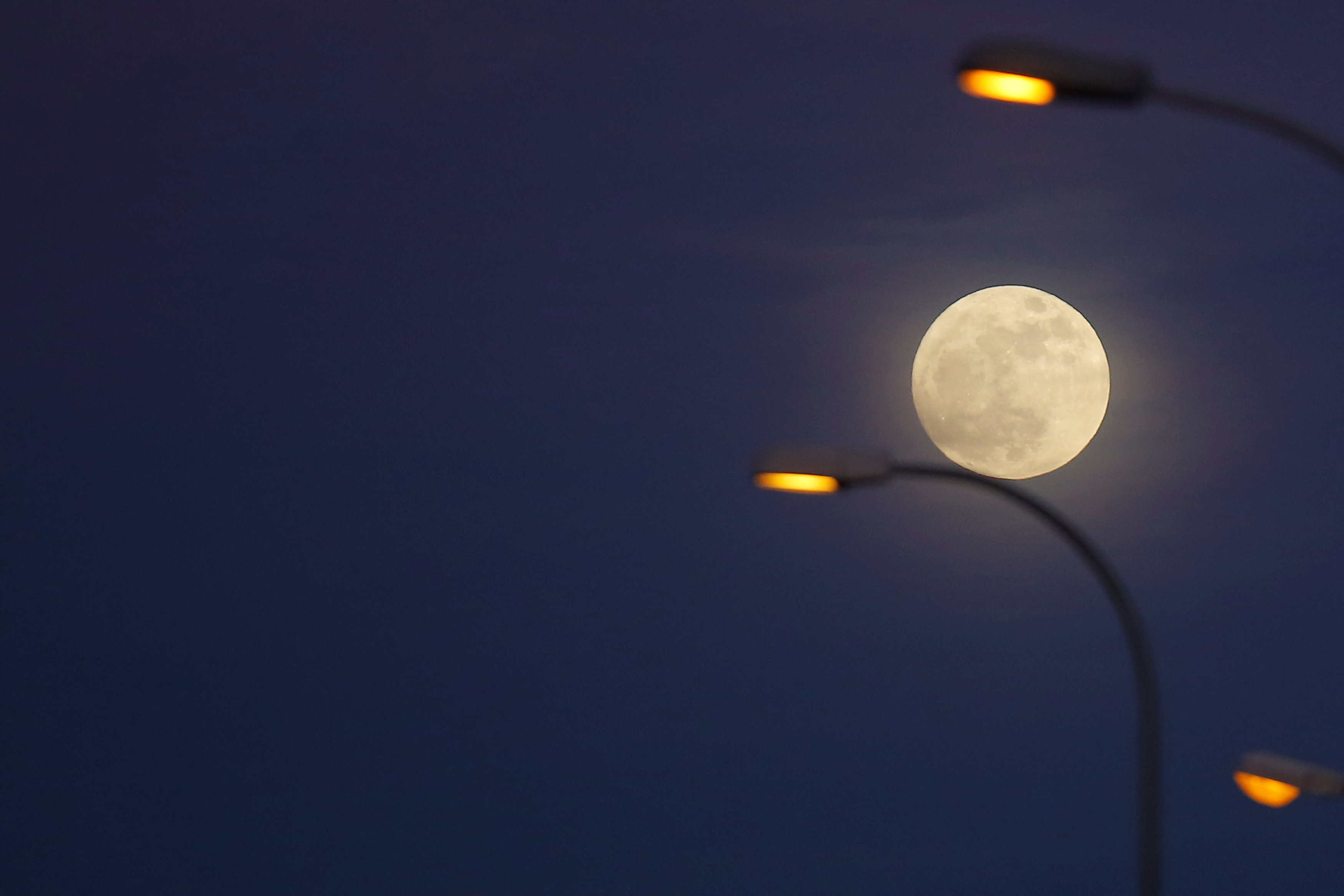 The 'supermoon' full moon is seen rising behind street lights in Ronda