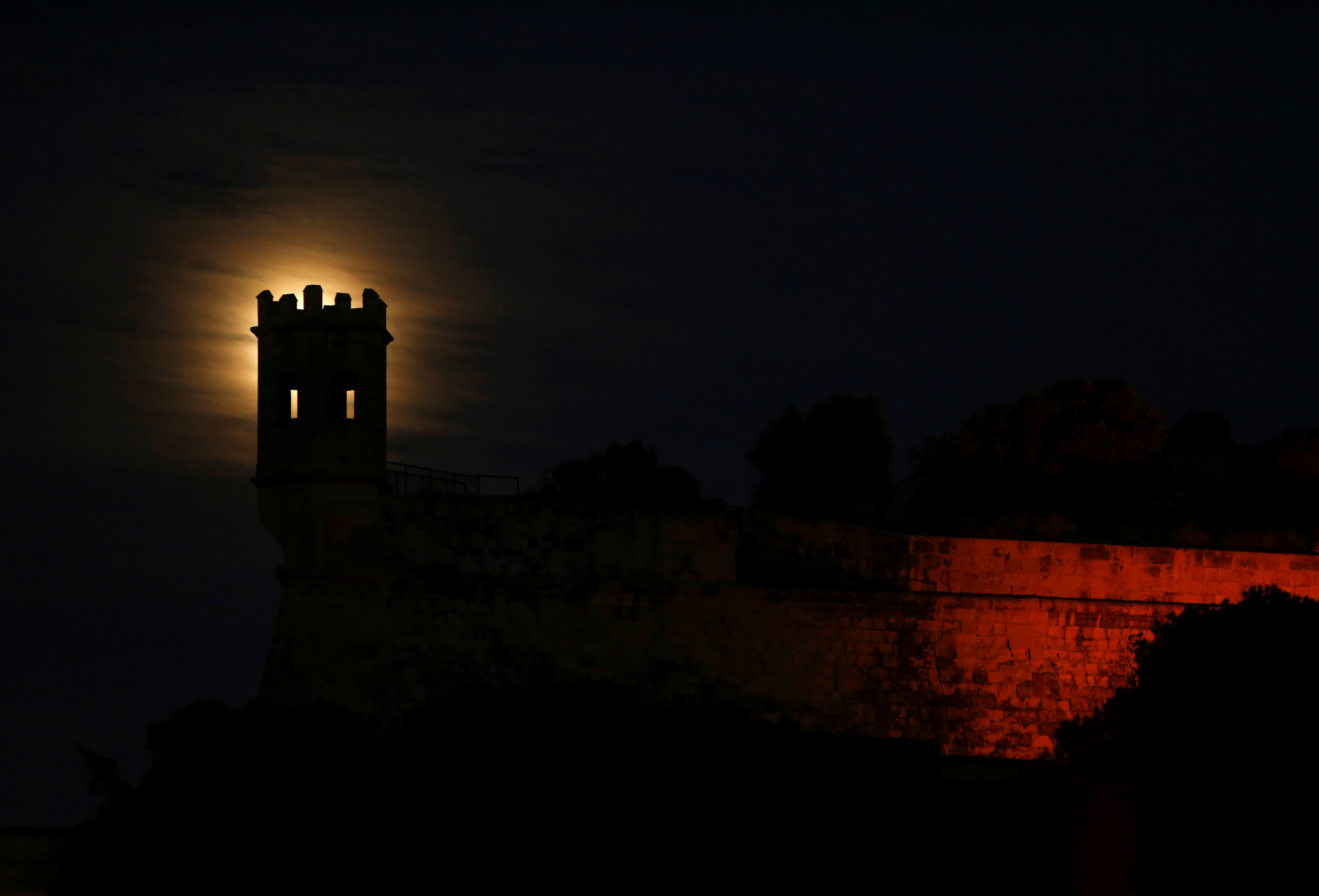 A 'supermoon' full moon rises behind the guard tower on the 17th century San Salvatore Bastion in Pieta