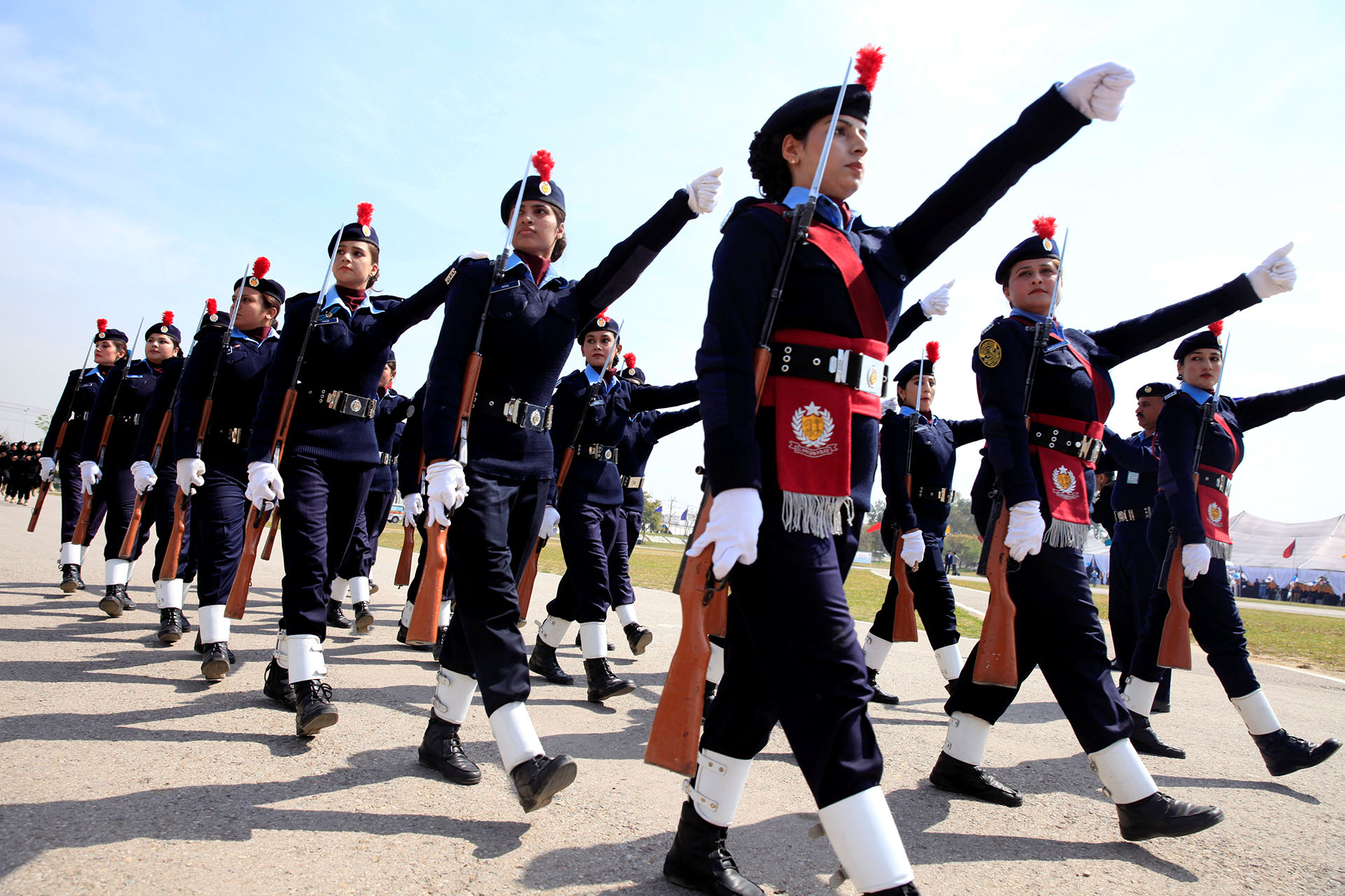 Female members of police forces march during a ceremony on International Women's Day, at the police headquarters in Islamabad