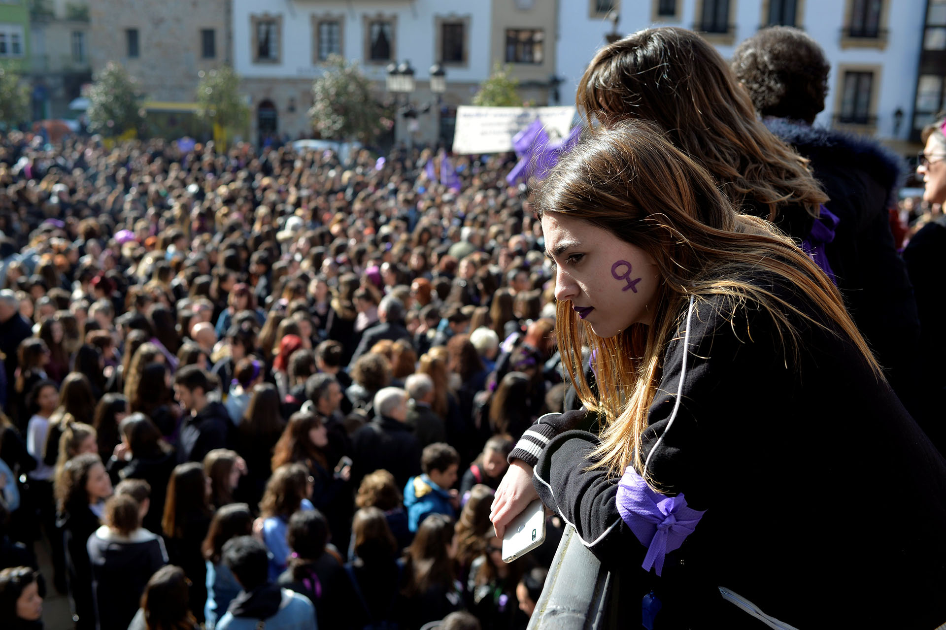 A woman with a female gender symbol on her cheek observes a demonstration for women's rights in Bilbao