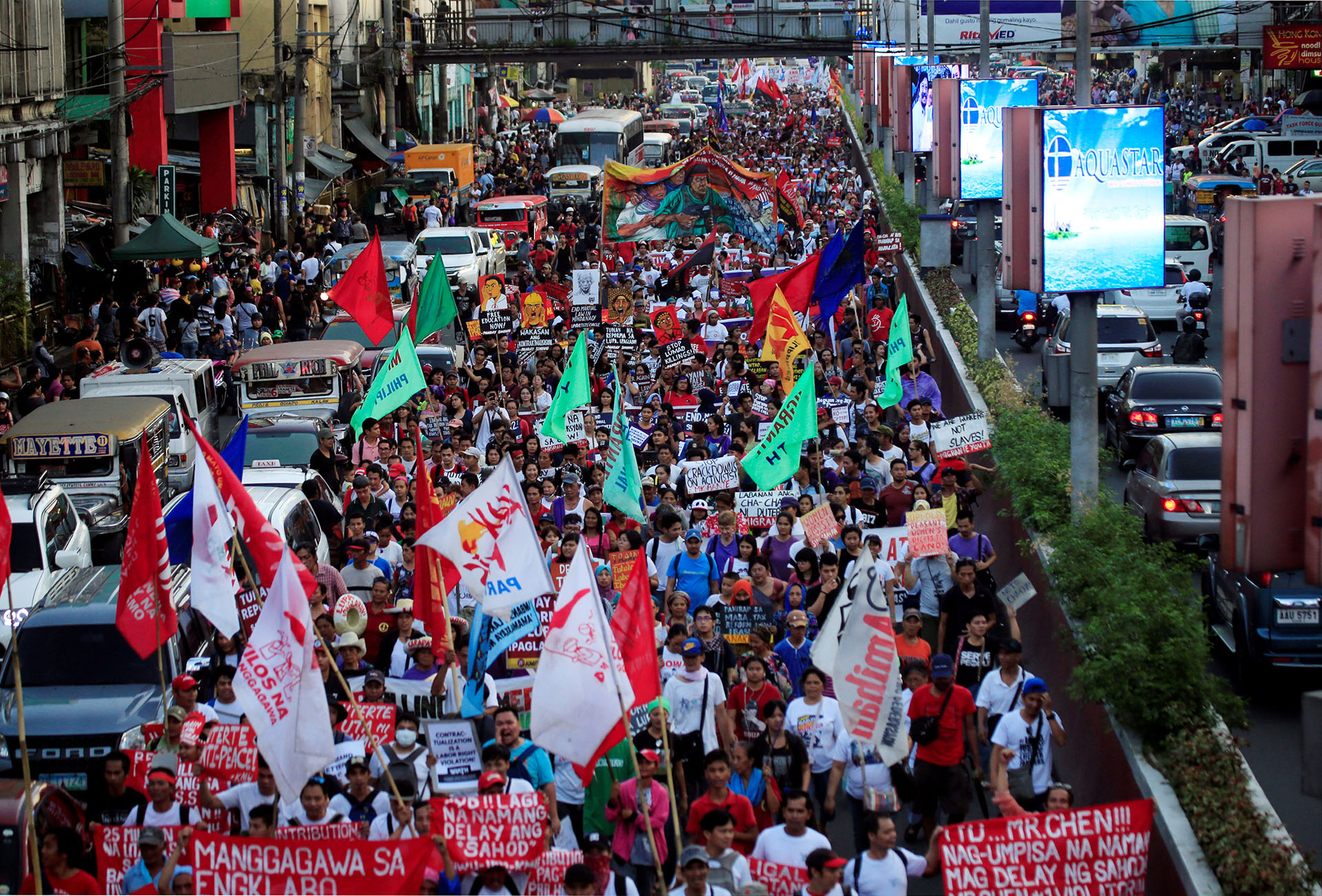 Women's rights activists display placards and streamers while marching during a celebration of the International Women's Day in Quiapo city, Metro Manila
