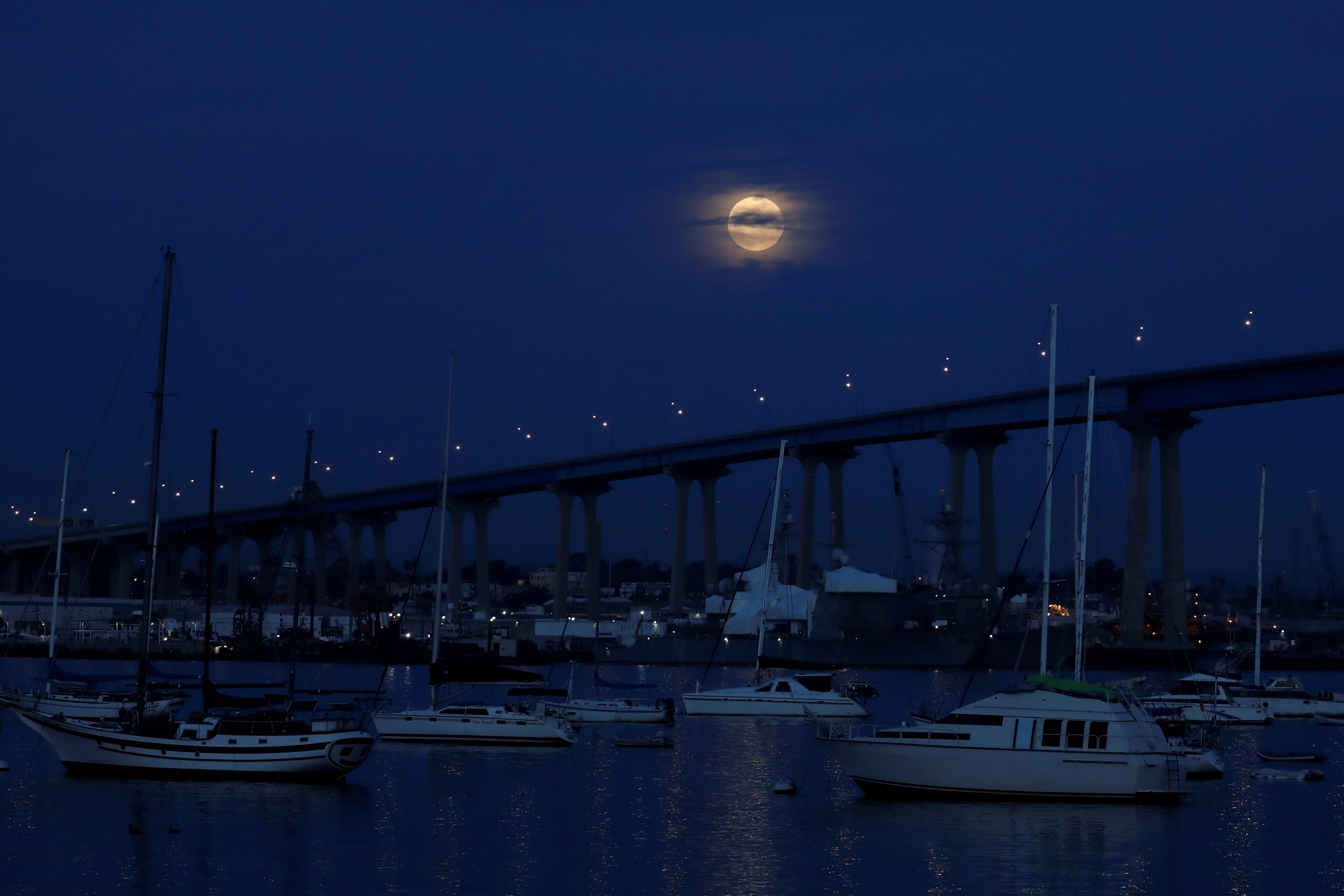 A full moon rises between clouds and above the Coronado Bridge before the start of a total lunar eclipse that is called a 'Super Blood Wolf Moon' in San Diego