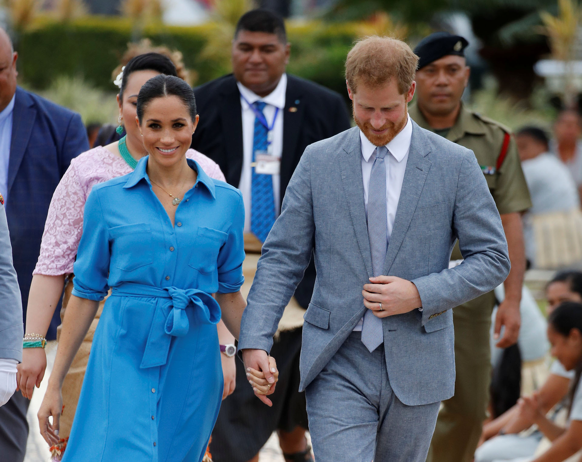 Britain's Prince Harry and Meghan, Duchess of Sussex walk together as they depart from Fua'amotu International Airport in Tonga