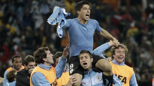 Uruguay's Luis Suarez, who stopped a last minute shot at goal by Ghana by using his hands, celebrates with team mates after their 2010 World Cup quarter-final soccer match at Soccer City stadium in Johannesburg