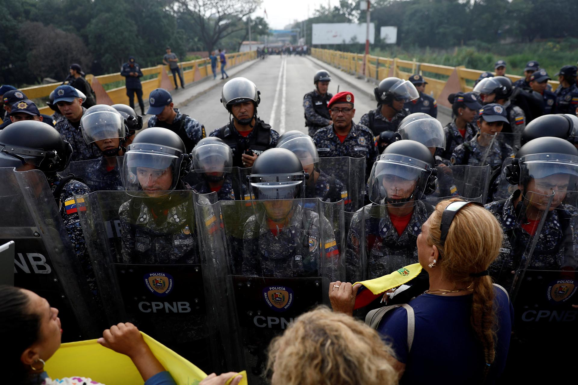 Venezuela's opposition supporters demand to cross the border line between Colombia and Venezuela at Simon Bolivar bridge as Venezuela's security forces stand in the border line blocking their way in the outskirts of Cucuta, Colombia