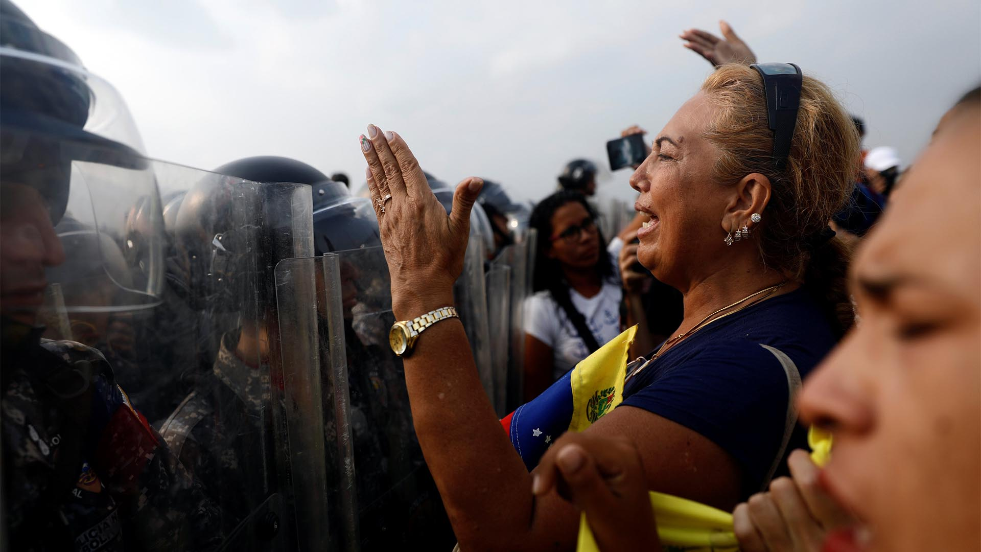Venezuela's opposition supporters demand to cross the border line between Colombia and Venezuela at Simon Bolivar bridge as Venezuela's security forces stand in the border line blocking their way