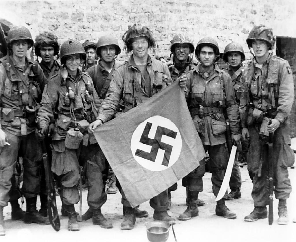 Tropas aerotransportadas estadounidenses mostrando una bandera nazi con la cruz gamada al centro.
