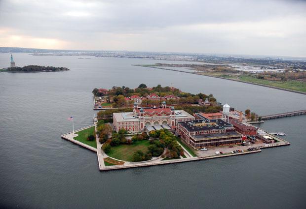Foto6: Vista aérea de Ellis Island. Se ve el edificio del museo y más atrás la Estatua de la Libertad. Foto: blog.myheritage.com